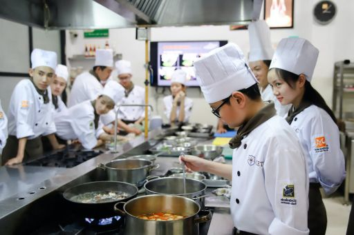 chefs standing near cooking pots inside kitchen