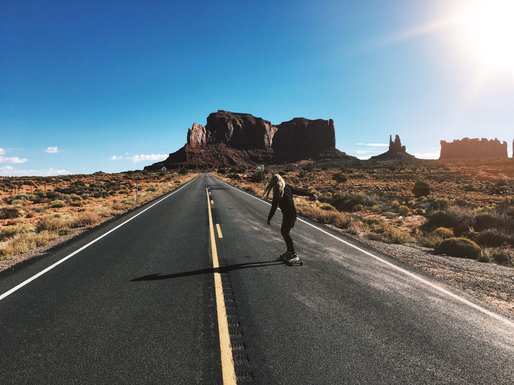 man in black jacket and black pants running on gray asphalt road during daytime